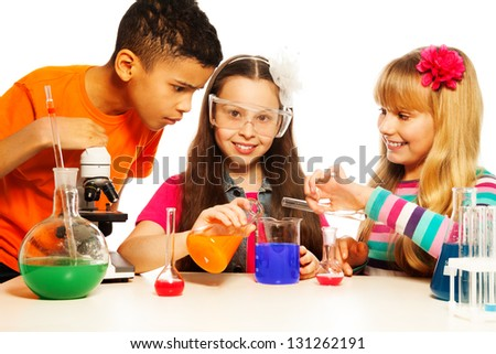 Three kids, two girls blond and brunet and black boy, with microscope, test tubes and flasks conducting experiments, isolated on white