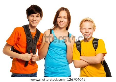 Three kids with school backpacks standing together - stock photo