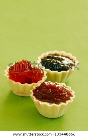 three kinds of jam in small edible treats over light green background