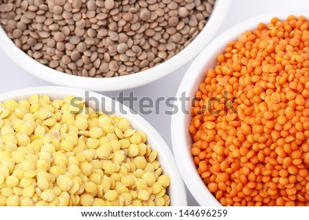 Three kinds of lentil in bowls - red lentil, yellow lentil and brown lentil