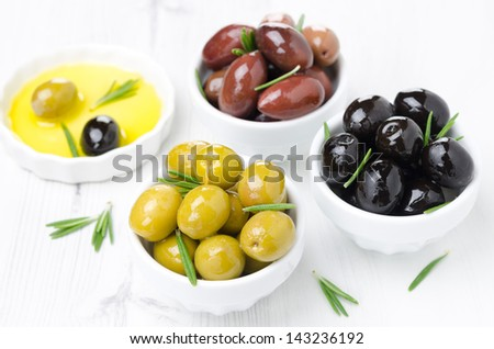 three kinds of olives in bowls, fresh rosemary and olive oil on a white background, horizontal
