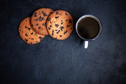 Three large cookies and a cup of coffee on a black concrete background. Cookies with chocolate.Image for inscription