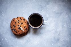 Three large cookies and a cup of coffee on a black concrete background.One cookie is broken into two pieces. Cookies with chocolate.Image for inscription