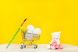 three large eggs in a supermarket cart with a paint brush and a cat toy in a pink pltye on a yellow background close up with space for text on the side