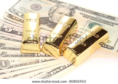 three large gold bars at many dollar bills