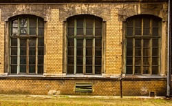 Three large old windows in an old disused building. Old brick  building with windows