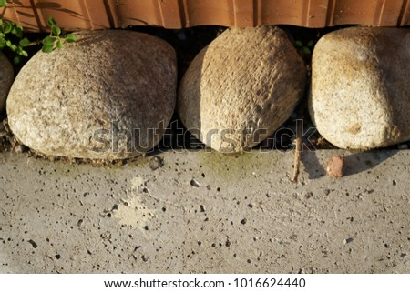 Three large stones in a cement floor are a confidence and tranquillity symbol, landscape design. #1016624440