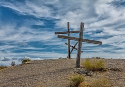 three large wooden ancient crosses on a sandy hill under a blue cloudy sky