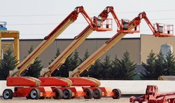 Three large work aerial platform lined up in an industrial site
