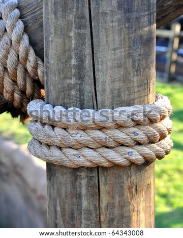 Three layers of rope tied around a wooden log, in the shade on a sunny day