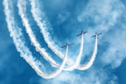 Three light-engine airplane perform aerobatics in a cloud of smoke