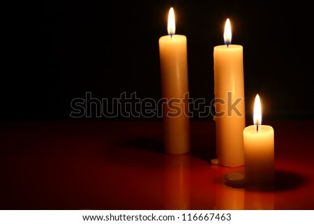 Three lighting candles on dark background with reflection