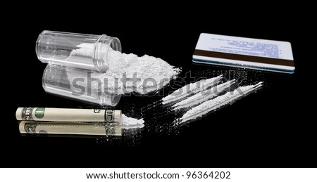 Three line of cocaine beside a wrapped up 100 dollar bill, credit card and vial of powder.