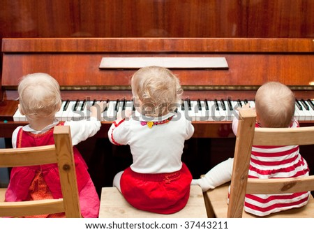 Three little baby girls playing a piano