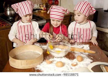 Three little chefs enjoying in the kitchen making big mess.