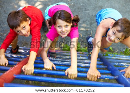 Three little children climbing ladder and looking at camera