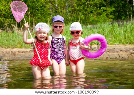 Three little cute girls go in water together