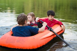 Three little friends floating in a rubber boat on the pond