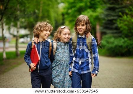 Three little friends go to school. Schoolchildren.