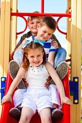 Three little friends on the playground slide