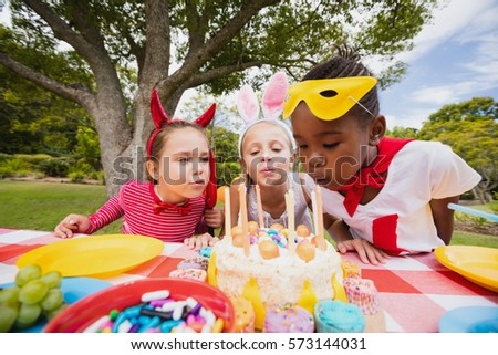 Three little girls blowing together birthday candles in the park #573144031