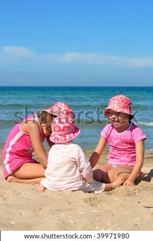 Three little girls playing on the beach