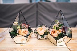 Three little glass vases with fresh bouquets stands on the table. Florarium