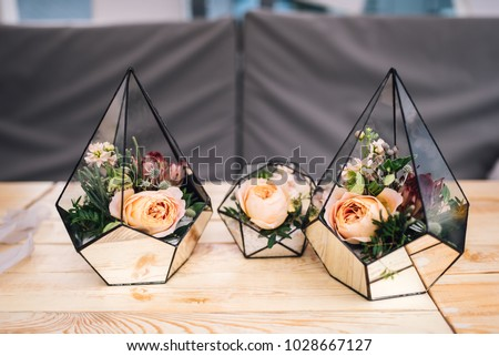 Three little glass vases with fresh bouquets stands on the table. Florarium #1028667127