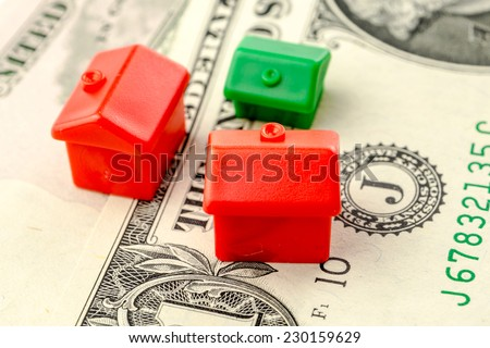 three little houses made of plastic are laying on one dollar banknote, business concept