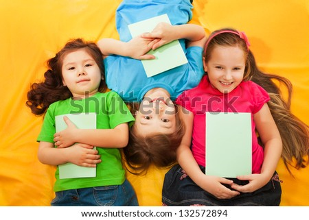 Three little kids, boys and girls, laying with books on the yellow mattress, smiling, with long hair,