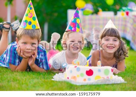 Three little kids celebrating birthday on green grass #159175979