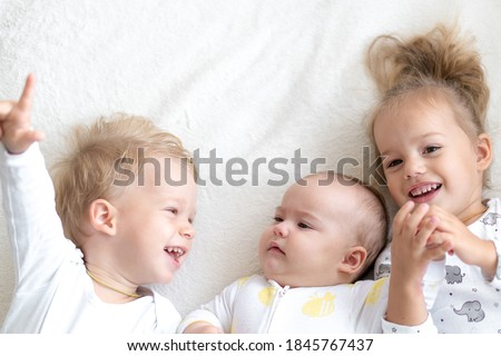 Three Little smiling kids play together on bed. Brother and sister show a newborn a toy. kids meeting new born sibling.Toddlers laugh and bonding. funny Children with small age difference.Copy space Foto stock ©