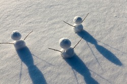 three little snowman in the winter season, the snowman is made of several parts and stands in the snow in cold weather, games in the snow with the creation of several snowman figures