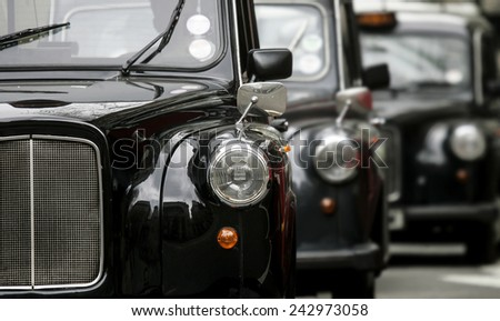 three London vintage cabs waiting in the street  - Shutterstock ID 242973058