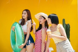 Three lovely young girl bestfriends wearing summer outfit over orange background. Summer vacation on the beach.