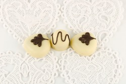 Three luxury chocolates on white hearts with copy space, sheer indulgence concept