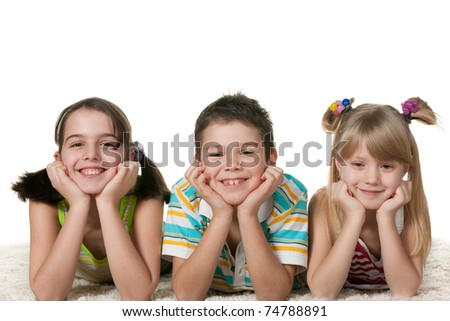 Three lying on the carpet children; isolated on the white background