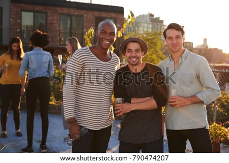 Three male friends at a rooftop party smiling to camera #790474207