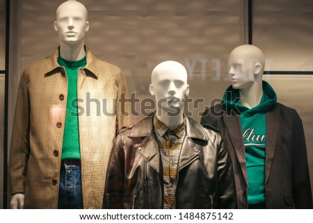Three male mannequins casual style in the window of a men's clothing store. Dummies in sweater, jumper, shirt and outerwear in showcase. Leather jacket, brown coat, black jacket and jeans. Shopping