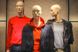 Three male mannequins sport casual style in the window of a men's clothing store. Dummies in sweater, hoody, jumper, jacket, outerwear in showcase. Winter autumn collection shopping
