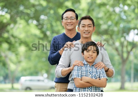 Three male members of Asian family smiling and looking at camera while standing on blurred background of park