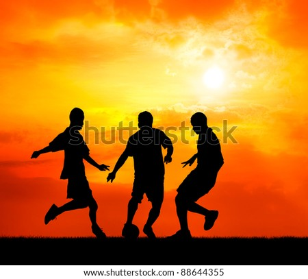 three man soccer player playing with ball during sunset silhouetted