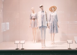 Three mannequins with summer clothes stand in a shop window in a shopping center. Summer clothes, white mannequins.