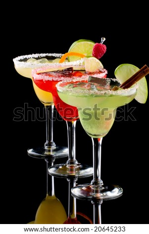 Three Margaritas - apple, orange and raspberry - in chilled glasses over black background, garnished with slice of green apple, limes, orange twist, raspberry and cinnamon stick.