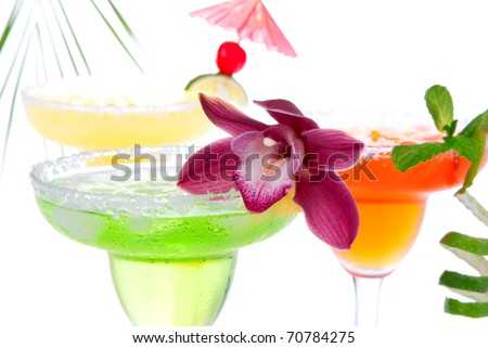 Three Margaritas cocktails composition decorated with lime, orchid, cherry, apple, peach and drink umbrella in margarita glasses  isolated on a white background