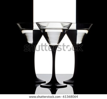 Three martini glass with alcohol on a black, white and black background