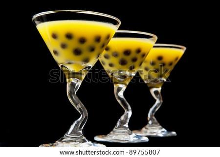 Three martini glasses of mango bubble tea on black