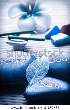 three massage stones - relax, body, soul - a candle, flower, aroma sticks and healing stone like a concept for wellness, reiki, body care and yoga symbols - stock photo
