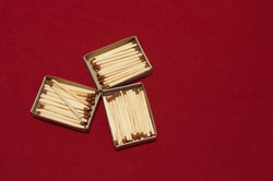 Three matchboxes with matches on a red background made of fabric with a small pattern.