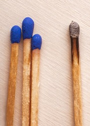 Three matches on wooden background next to burnt match. Self isolation symbol
